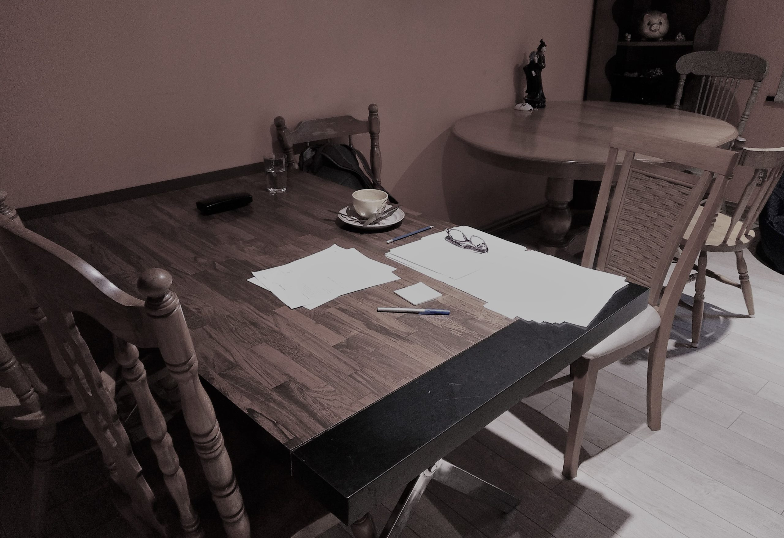 Table with writing papers, pen, coffee cup and glasses